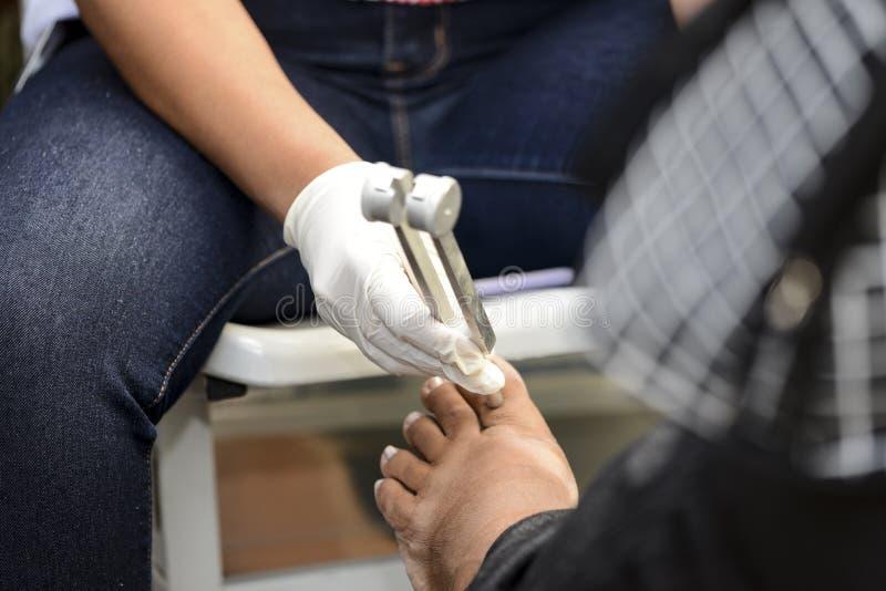 Sjukvårdprofessionelln undersöker foten av en diabetisk patient med en monofilament i en avskärma aktion fotografering för bildbyråer