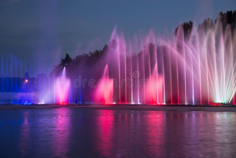 sjunga för barcelona springbrunnliggande Glödande kulöra springbrunnar och laser-show royaltyfria foton