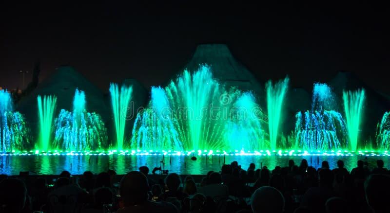 sjunga för barcelona springbrunnliggande Glödande kulöra springbrunnar och laser-show arkivfoton