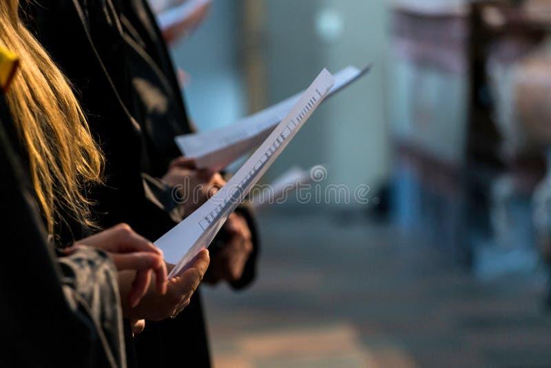 Sjunga i kör sångare som rymmer den musikaliska ställningen och sjunger på studentgradu arkivfoto