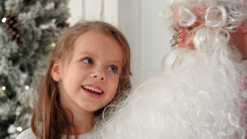 Sjungande julsång för gullig liten flicka samman med Santa Claus arkivfoto