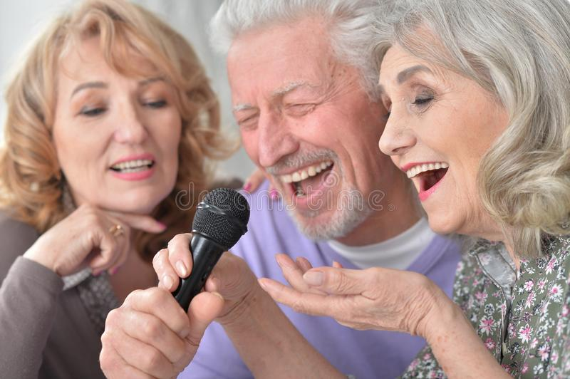 Sjungande karaoke för högt folk med bärbara datorn, medan dricka te royaltyfria foton