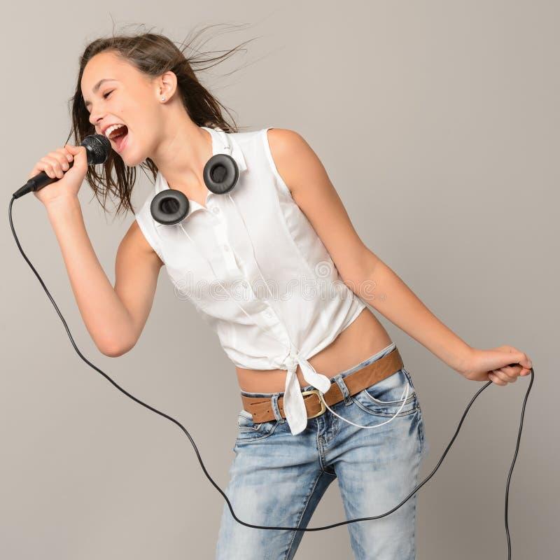 Sjungande tonårs- flicka med mikrofonkaraokemusik arkivfoton