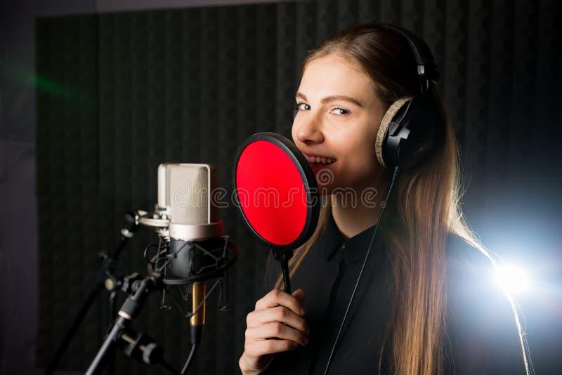 Sjungande ung flicka i inspelningstudio royaltyfria foton