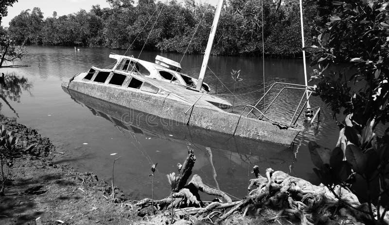 Sjunken riden ut skrov för herrelöst gods delvist av en vit motorisk yacht arkivfoton