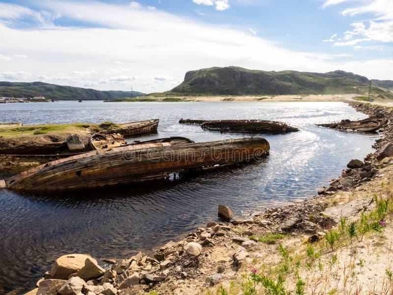 Sjunkna gamla träfiskebåtar i Teriberka, Murmansk Oblast, Ryssland arkivbilder
