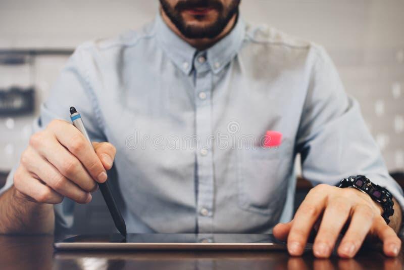 Skäggig affärsman som arbetar på minnestavlan med nålen AffärsmanH royaltyfri fotografi