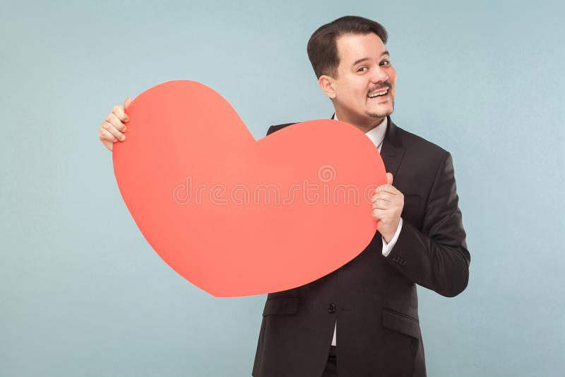 Skäggig affärsman som rymmer stor röd hjärta och toothy le royaltyfria bilder