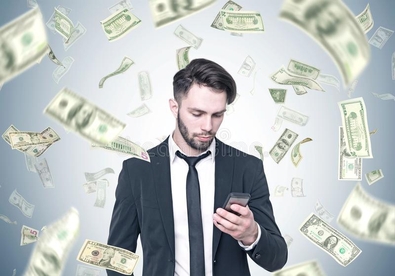 Skäggig affärsman som ser smartphonen, dollarregn arkivfoton
