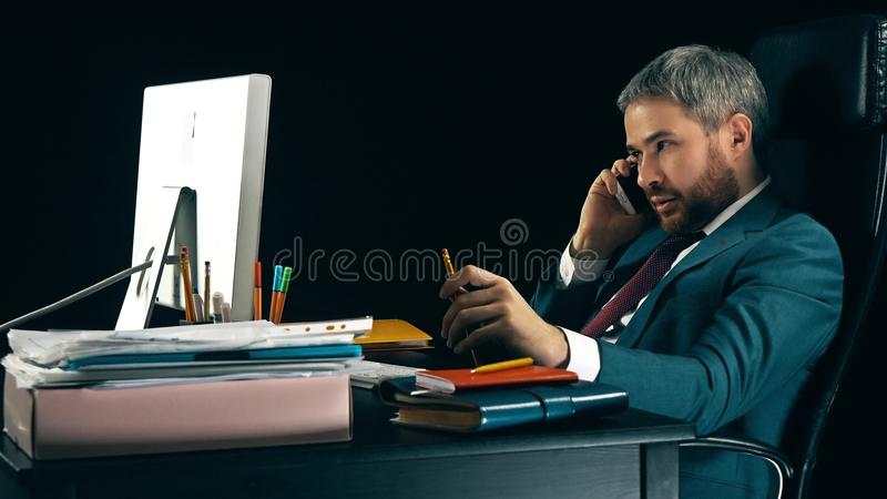 Skäggig affärsman som talar på hans mobiltelefon Mörk bakgrund som isoleras arkivbilder