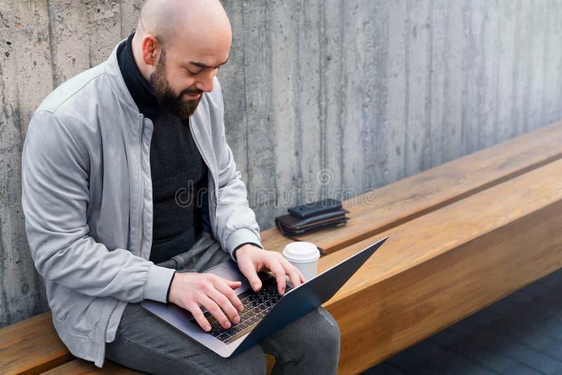 Skäggig affärsmanfreelancer som utomhus arbetar på bärbara datorn Manmaskinskrivning p? b?rbar datortangentbordet Avlägset arbete arkivfoton