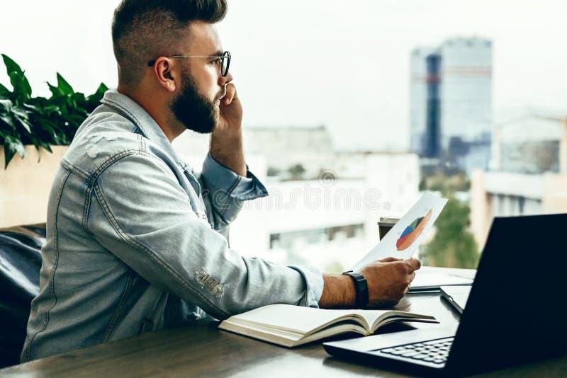 Skäggig affärsmanhipster som talar på telefonen, medan sitta på skrivbordet i regeringsställning, håll dokument, ledset seende fö royaltyfria foton