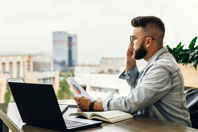 Skäggig affärsmanhipster som talar på telefonen, medan sitta på skrivbordet i regeringsställning, håll dokument, ledset seende fö royaltyfri bild