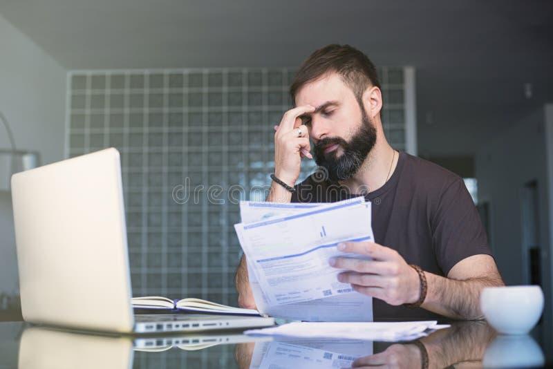 Skäggig allvarlig koncentrerad man som arbetar på bärbara datorn och sitter på tabellen, medan se legitimationshandlingar och rym arkivfoton
