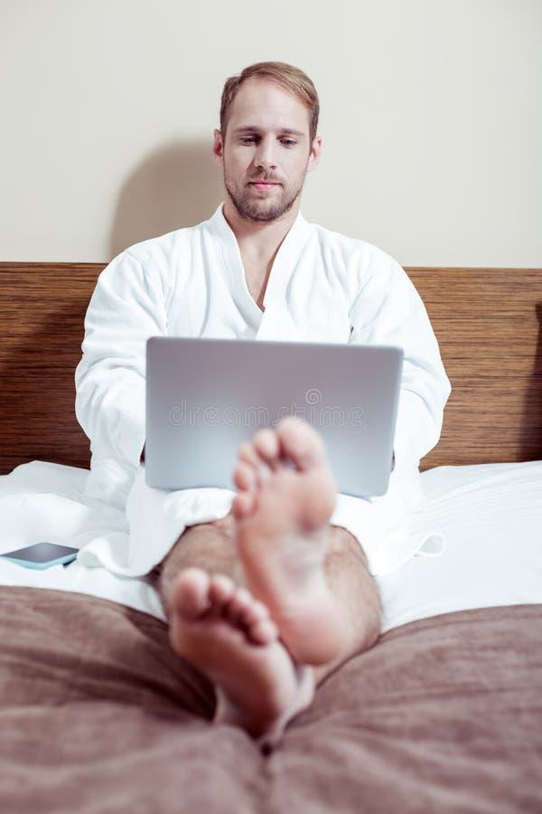 Skäggig angenäm man som rymmer hans silverbärbar datorarbete i säng arkivbild