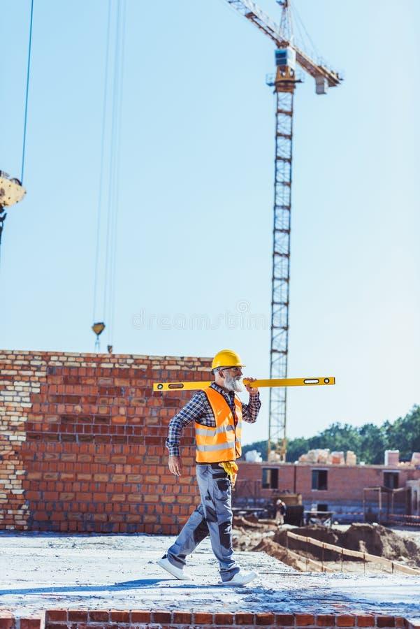 Skäggig arbetare i reflekterande väst och hardhat som går med andenivån across arkivfoto