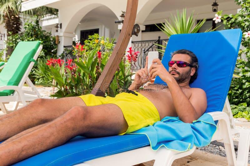 Skäggig Caucasian man med solglasögon genom att använda smartphonen på sunbed i en semesterort arkivfoton