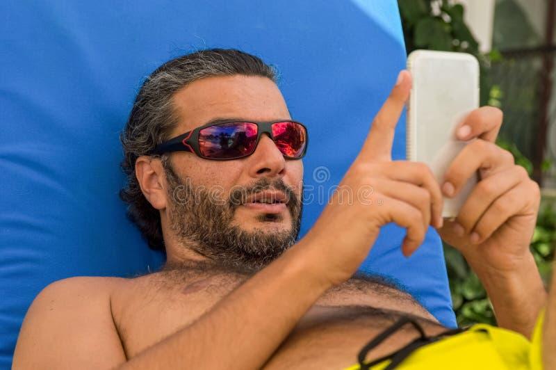 Skäggig Caucasian man med solglasögon genom att använda smartphonen på sunbed i en semesterort royaltyfri bild