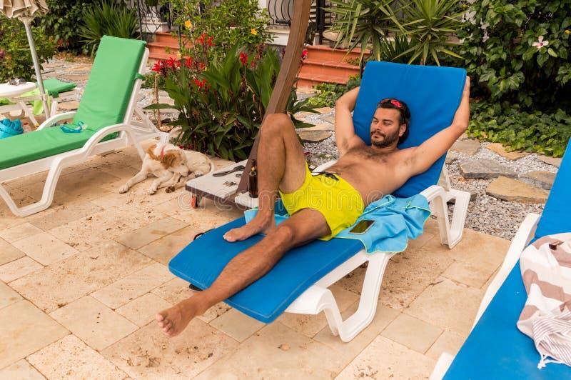 Skäggig Caucasian man med solglasögon som vilar på sunbed i en semesterort arkivfoto
