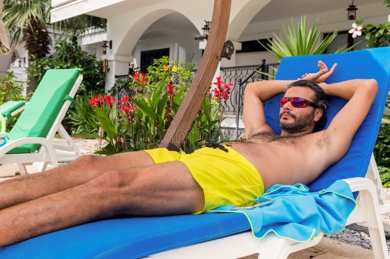 Skäggig Caucasian man med solglasögon som vilar på sunbed i en semesterort fotografering för bildbyråer