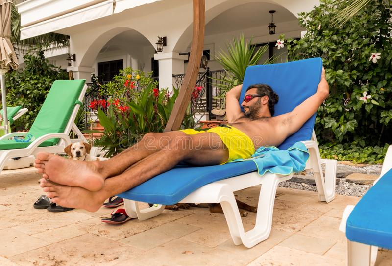 Skäggig Caucasian man med solglasögon som vilar på sunbed i en semesterort royaltyfria bilder