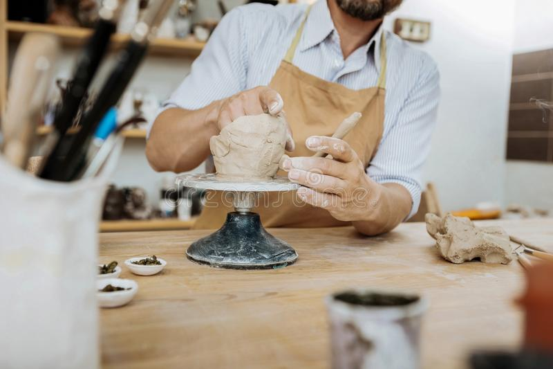 Skäggig ceramist som har idérika idéer, medan genom att använda keramikgrejen arkivbild