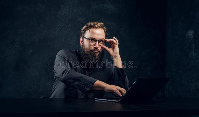 Skäggig chef som arbetar bak en bärbar dator fotografering för bildbyråer