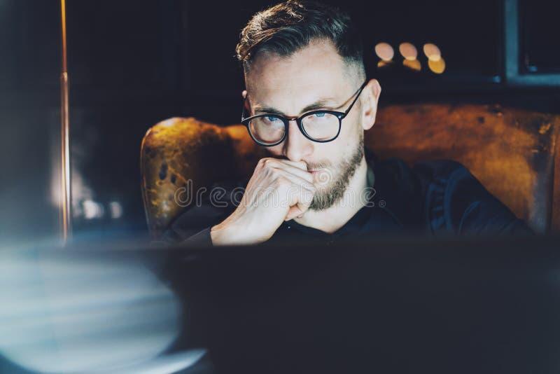 Skäggig chef som arbetar det moderna vindkontoret Mansammanträde i tappningstol på natten, nytt startup projekt för thinkig använ arkivbilder