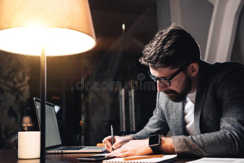 Skäggig coworker som arbetar vid den wood tabellen med bärbara datorn Den idérika affärsmannen gör ny start på nattvindkontoret A arkivfoton