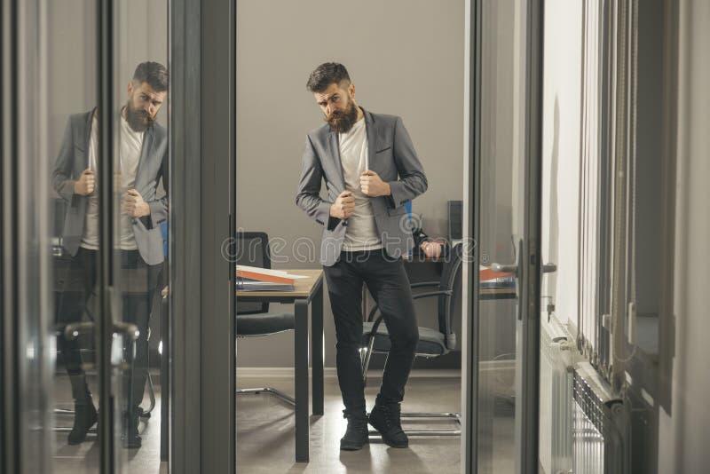 Skäggig dörr för kontor för manblick ut Skäggig man i det moderna kontoret med glasväggar, affärslivsstil royaltyfri bild