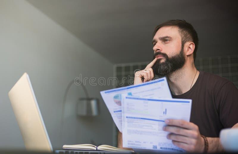 Skäggig eftertänksam man som arbetar på bärbara datorn och sitter på tabellen, medan se legitimationshandlingar och rymma hans hu arkivfoto