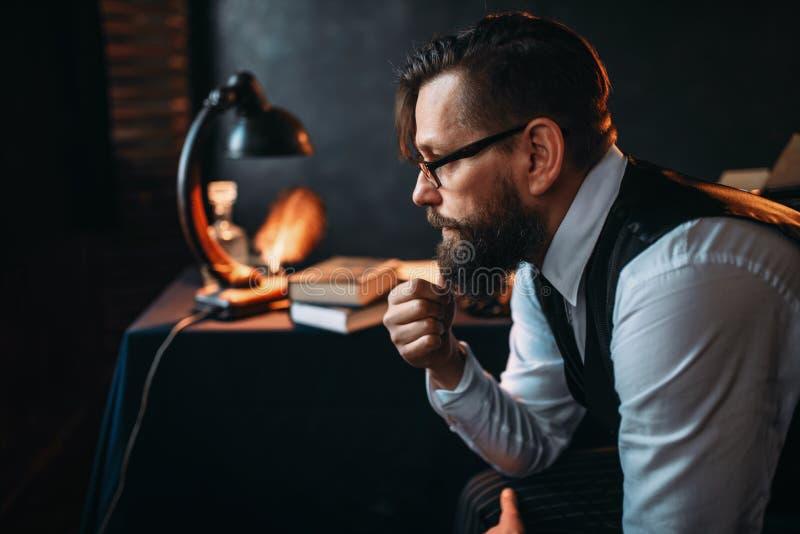 Skäggig författare i exponeringsglas som röker ett rör fotografering för bildbyråer