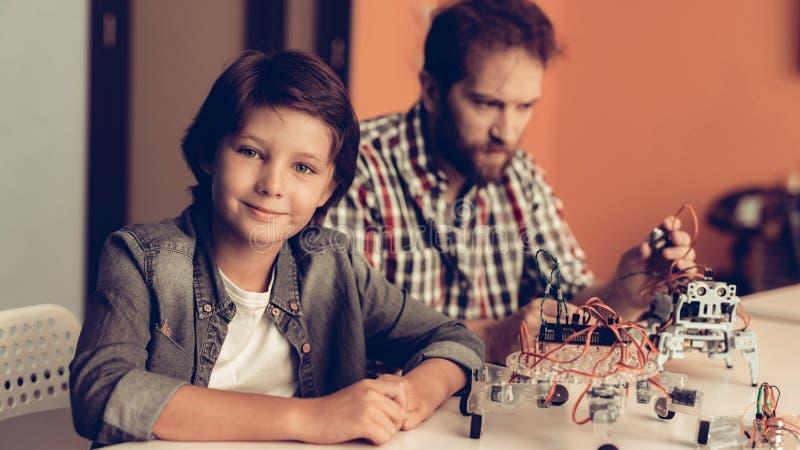 Skäggig fader och son som hemma konstruerar roboten royaltyfri fotografi