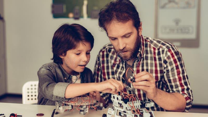 Skäggig fader och son som hemma konstruerar roboten arkivfoto