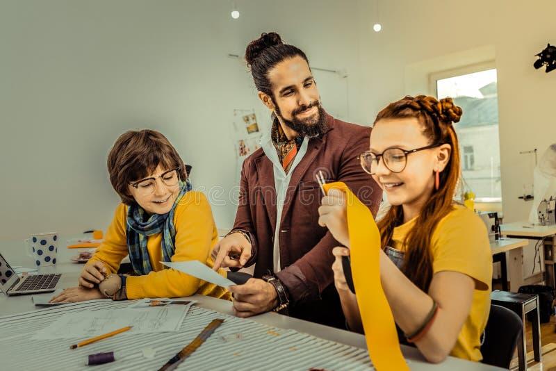 Skäggig faderkänsla som är stolt av hans barn som deltar i designskola fotografering för bildbyråer