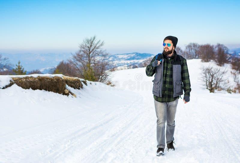 Skäggig fotvandrare som går på det dolda berget för snö arkivbilder
