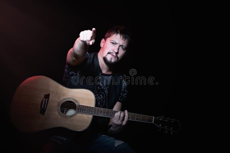Skäggig gitarrist som pekar fingrar på tittaren royaltyfri bild