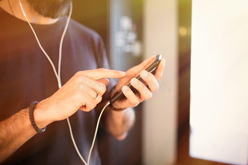 Skäggig grabb som bär tillfällig grå t-skjorta lyssnande musik i hörlurar som kontrollerar sociala nätverk på smartphonen  royaltyfria foton