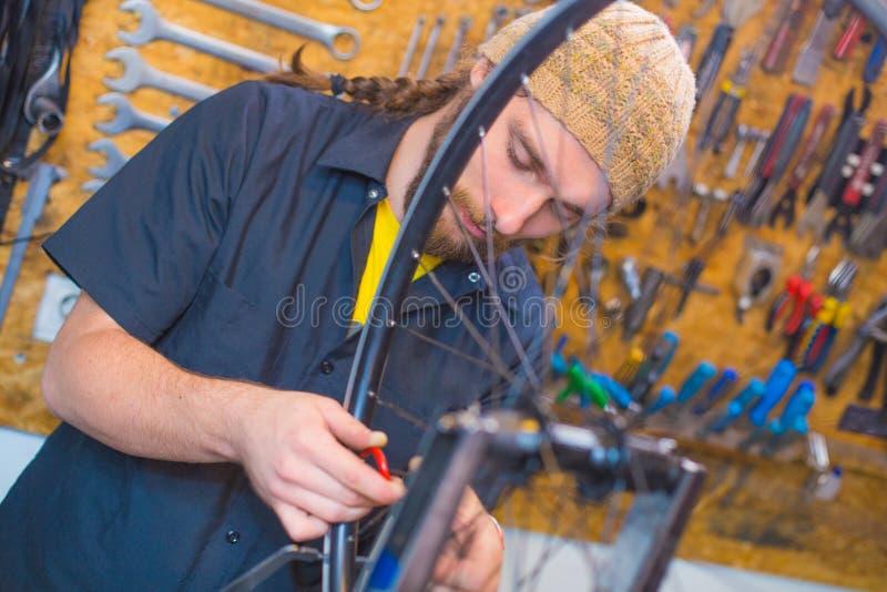 Skäggig grabb som reparerar cykeln i seminariet arkivbilder