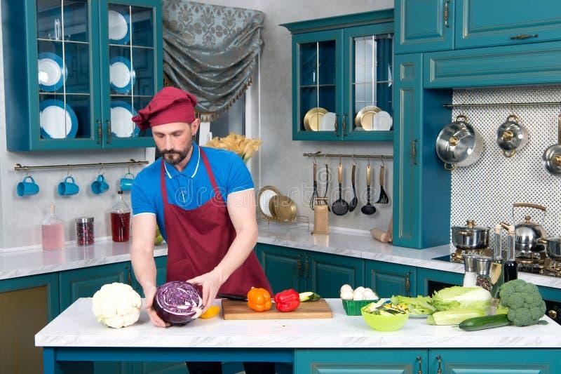 Skäggig grabbkock i förkläde och lock Kock som klipper röd kål för matställe arkivbilder