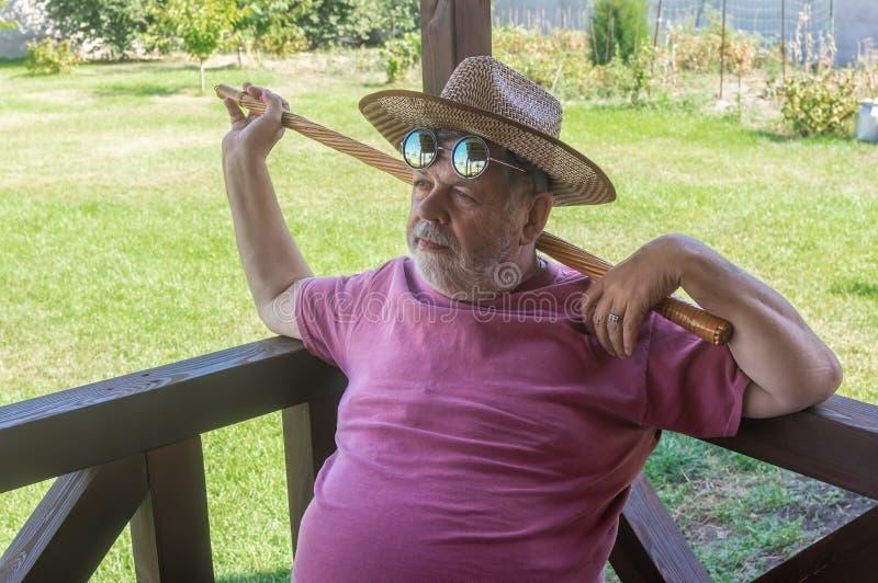 Skäggig hög man i rund solglasögon som vilar, medan sitta på verandan royaltyfri bild