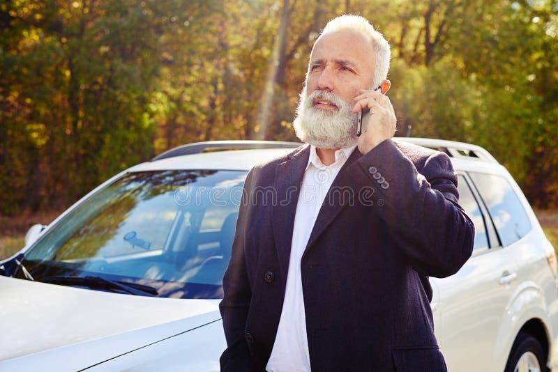 Skäggig hög man som talar på telefonen royaltyfri bild