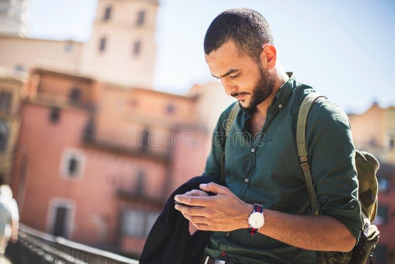 Skäggig handelsresande för barn som använder hans smartphone royaltyfria bilder