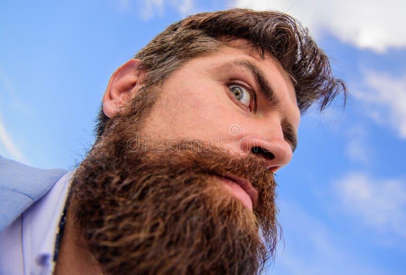 Skäggig hipster för man med mustaschhimmelbakgrund Kontrollera ut mitt långa skägg Ultimat mustasch som ansar handboken hipster royaltyfria bilder