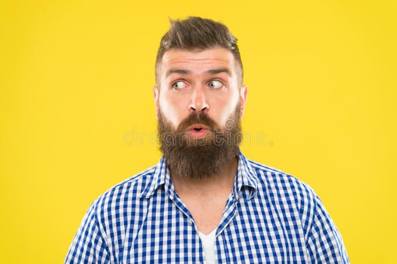 Skäggig hipster för man som undrar upp gult bakgrundsslut för framsida Förvånat framsidauttryck för grabb Hipster med skägget och arkivfoto