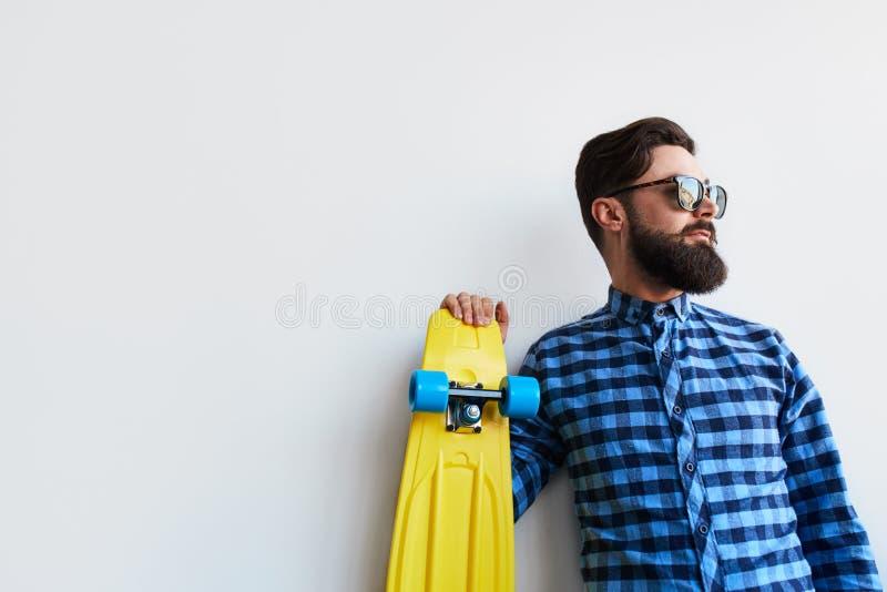 Skäggig hipster i rutig skateboard för skjortainnehavguling fotografering för bildbyråer