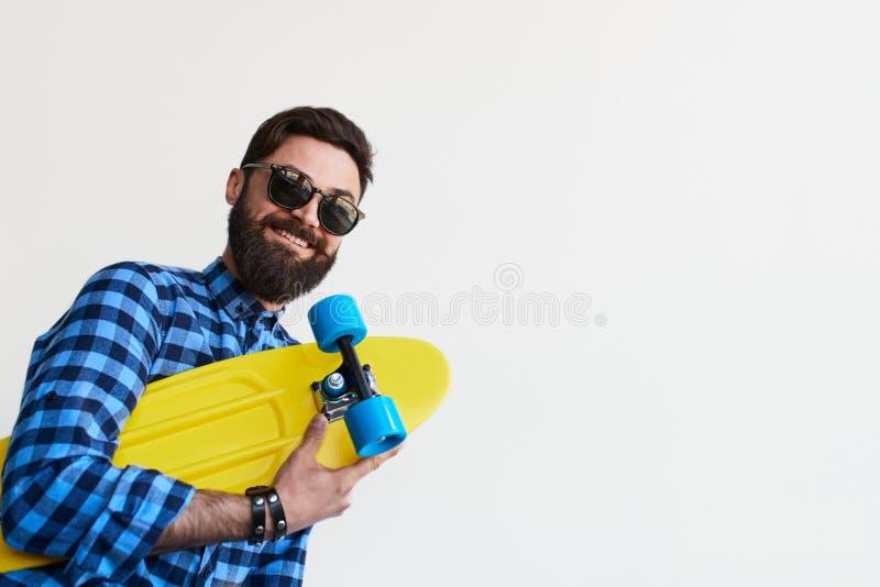 Skäggig hipster i rutig skateboard för skjortainnehavguling royaltyfria foton