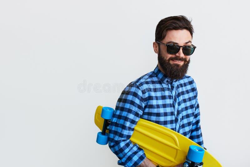 Skäggig hipster i rutig skateboard för skjortainnehavguling arkivbilder