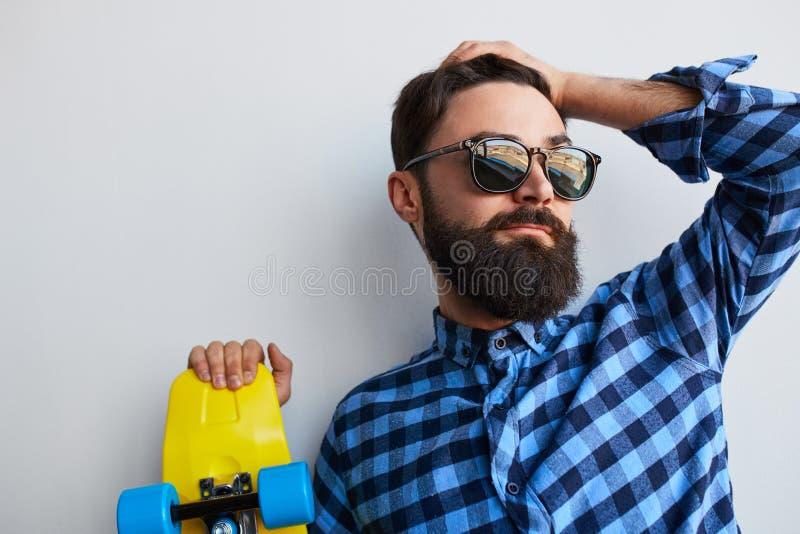 Skäggig hipster i tillfällig blå skjorta med skateboarden royaltyfria bilder