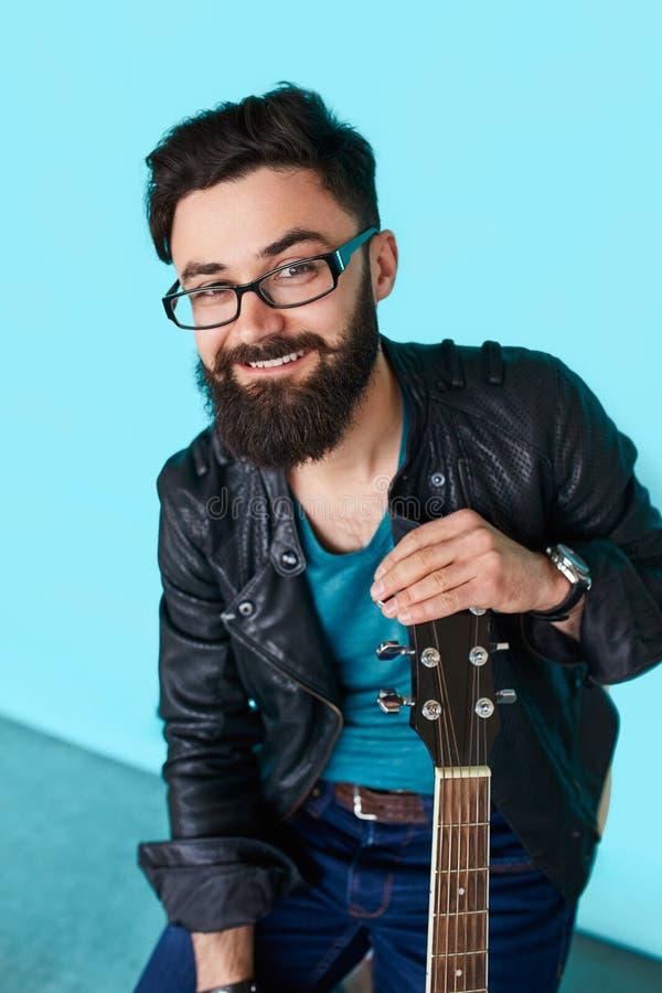 Skäggig hipsterman för slut som rymmer den akustiska gitarren royaltyfri bild